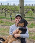 Raquel Kallas sitting with a dog in a New Zealand vineyard